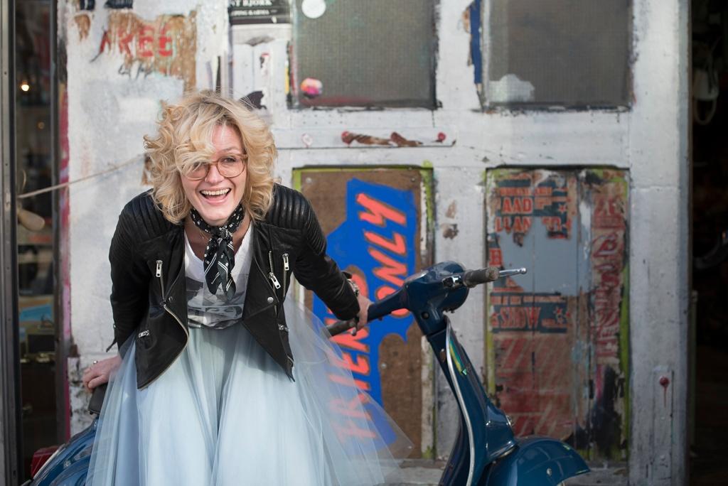 Foto für Tinder. Eine Frau trägt eine Lederjacke und posiert mit einem Vespa.